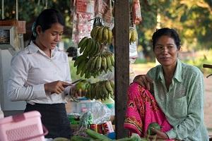 Aasialasiet naiset myyvät kojusta banaaneja.