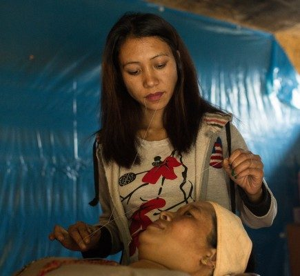 Susmita Shrestha muotoilee Sona Laxmi Shresthan kulmakarvat. Kuva: Ville Asikainen.