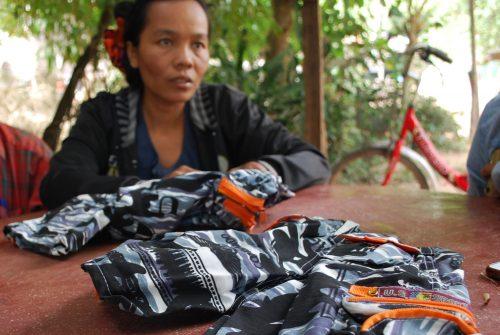 Yrittäjänainen ompelee lasten housuja Siem Reapin kylässä.