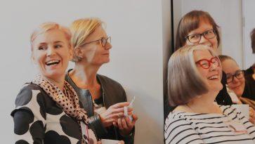 Ryhmä naisia kuuntelemassa esitystä. Etualalla oleva nainen katsoon nauraen kameraan.