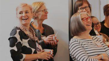 Joukko naisia nojailee seinää vasten ja nauraa yhdessä.
