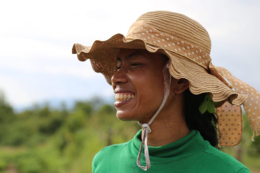 Aasialainen nainen olkihattu päässään katsoo hymyillen vasemmalle.