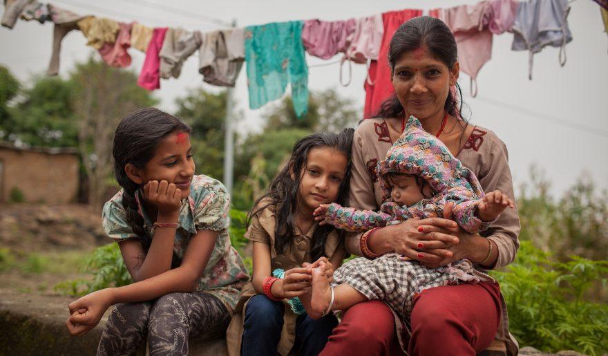 Naisten Pankin toiminnassa mukana oleva nepalilainen nainen istuu kolmen lapsensa kanssa pihalla. Taustalla on pyykkiä kuivumassa.