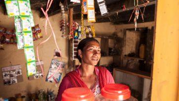 Aasialainen nainen seisoo hymyillen kaupan myyntiskin takana.