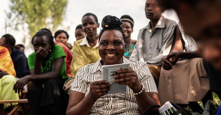 Hymyilevä nainen istuu vihko kädessä. Taustalla useita iloisia ihmisiä.