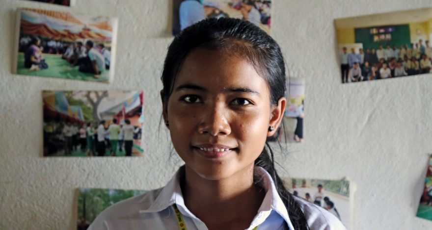 Nuori nepalilainen opiskelijatyttö Srey Ny katsoo kameraan huoneessaan.