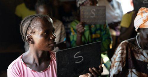 Nainen pitää kädessään piirtotaulua, johon hän on kirjoittanut S-kirjaimen. Taustalla muita lukuopintoja suorittavia naisia.