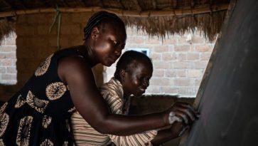 Afrikkalainen opettaja auttaa oppilastaan kirjoittamaan liitutaululle.