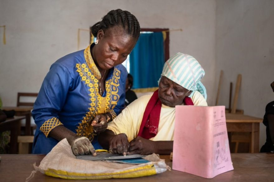 Ugandalainen lukutaito-opettaja opettaa lukutaitoryhmän oppilasta