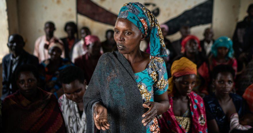 Ungandalainen Loyce Bukumi puhuu säästöryhmän kokouksessa. Taustalla naisia.