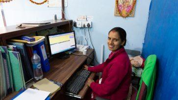 Aasialainen nainen situu tietokoneen ääressä ja katsoo kameraan päin.