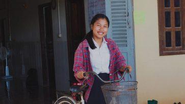 Tyttö seisoo kotinsa edessä ja pitelee kiinni polkupyörästään.