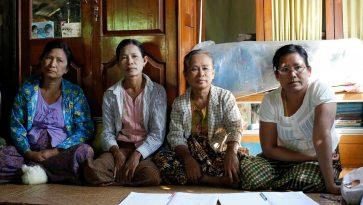 Neljä Myanmarin naisten ryhmän naista istuu pyödän takana. Pöydällä on papereita.