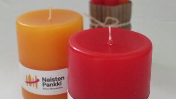 Kuvassa kaksi pyötäkynttilää ja taustalla nippu korkeita kynttilöitä