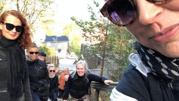 Ryhmä naisia katsoo hymyillen kameraan ulkokuntoportaissa.