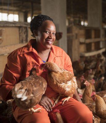 Afrikkalainen nainen pitelee sylissään kanaa.