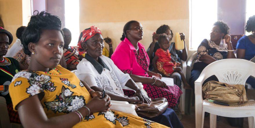 Ryhmä afrikkalaisia naisia istuu kuuntelemassa kirkossa kuuntelemassa rauhanneuvotteluja.