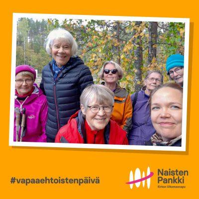 Seitsemän naista katsoo kameraan hymyille metsän keskellä.