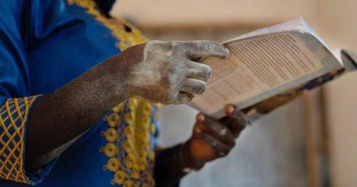 Afrikkalaisen naisen kädet pitelevät kirjaa.