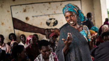 Afrikkalainen nainen seisoo keskellä istuvia naisia ja selittää asiaansa katsoen kameraan.