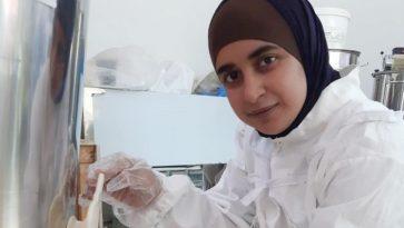 Nainen suojapuvussa laskee metallitynnyristä hunajaa lasipurkkiin.