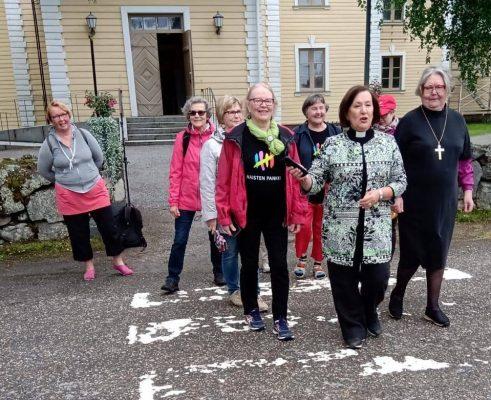 Ryhmä naistenpankkilaisia piispa emerita Irja Askolan ja kirkkoherran kanssa lähdössä kävelemään.