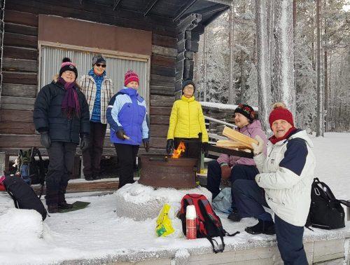 Kuusi iloista naista laavulla talvisessa säässä.