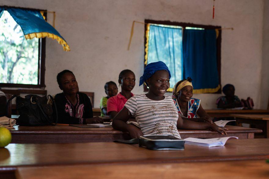 Luokassa istuvia naisia. Etualalla nainen nojaa takana olevaan pulpettiin.