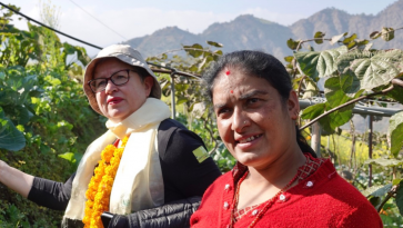Vapaaehtoinen ja nepalilainen nainen viljelyksillä