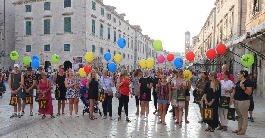 Joukko naisia seisoo värikkäät ilmapallot käsissään.