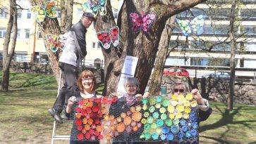 Kolme naista seisoo ulkona keväisessä säässä ja pitelee kanaverkkoa, jossa on värikkäitä virkattuja kukkia. Mies on tikkailla ja puihin on kiinnitetty kirjavia virkattuja perhosia.