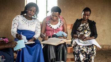 Kolme afrikkalaista naista istuu vierekkäin kirjoittaen lehtiöihin.