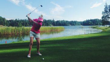 Nainen golfaamassa rantamaisemissa.