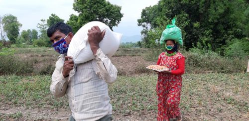 Nepalilainen mies kantaa ruokasäkkiä ja takana kävelevällä naisella on pään päällä jauhopussi.