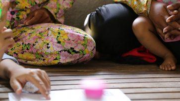 Kukkakuvioisen mekon helma ja pystyssä oleva sormi esittämässä paperille kirjoitettua asiaa.