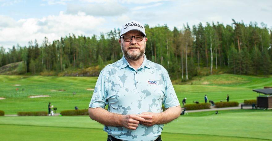 Mies lippalakkipäässä seisoo golfkentällä ja katsoo kameraan.