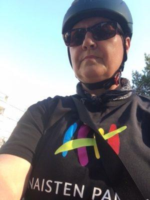 Naistenpankkilainen Jaana Heporanta toimittamassa pyörällä kahvia tilaajille pyörällä Naisten Pankin paita päällä.