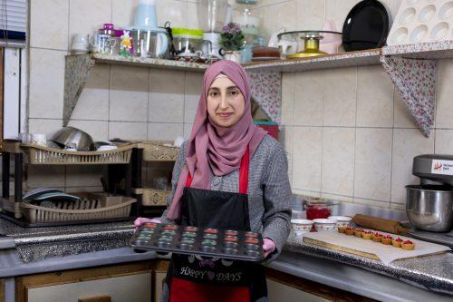 Esraa Al-Sehaiti seisoo keittiössä ja pitelee pellillistä herkkuja.
