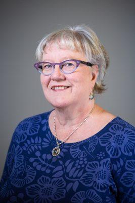 Ulla Sarasalmi katsoo kameraan päällään sininen paita.