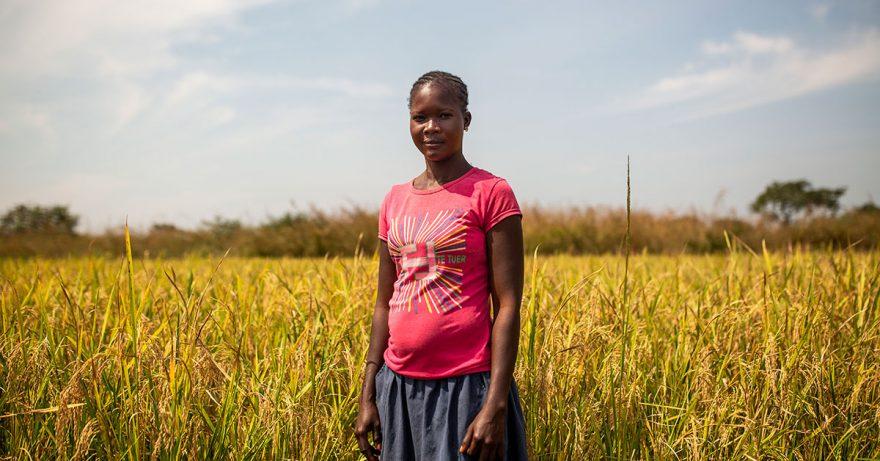 Nainen seisoo pellon edessä ja katsoo kameraan
