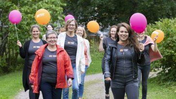 Joukko naisia kävelee ilmapallot käsissään.