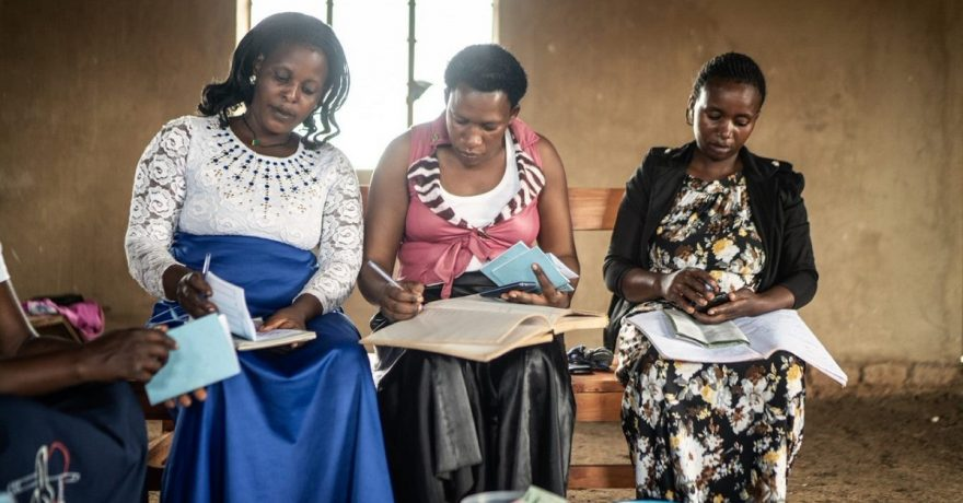 Kolme naista istuu tuoleilla ja tutkii sylissänsä olevia tilikirjoja.