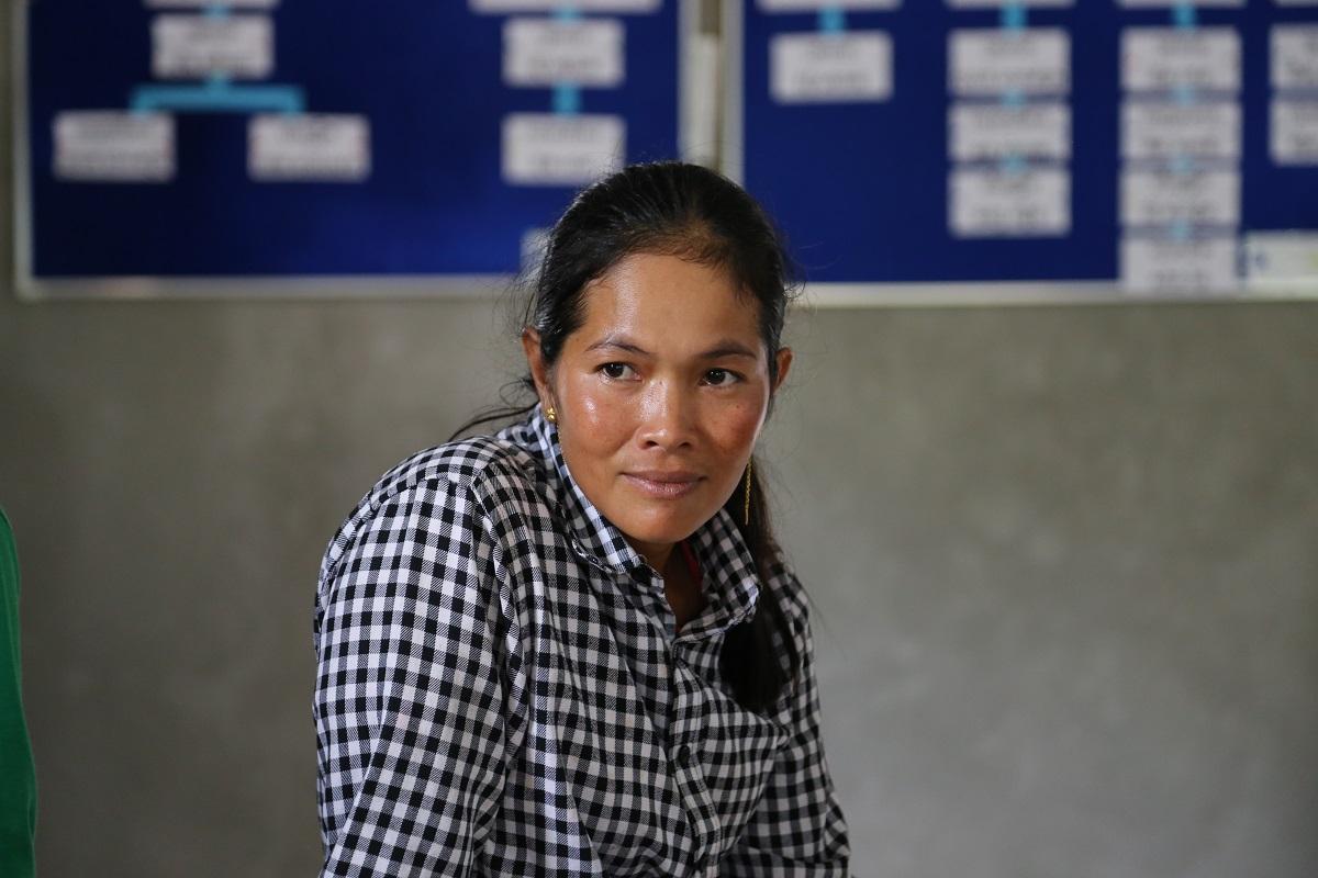 Nainen ruudullisessa paidassa istuu koululuokassa .