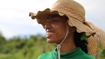 Hattupäinen nainen hymyilee kameralle.