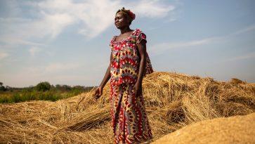 Nainen värikkäissä vaatteissa seisoo heinäarolla.